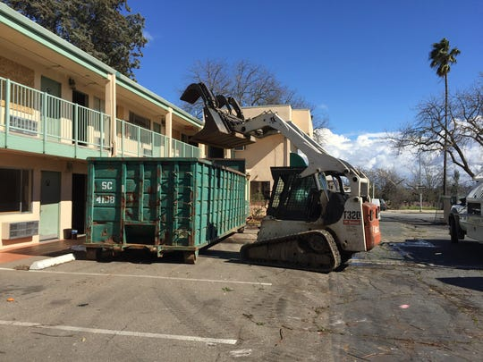 Crews with Gabel's Hauling & Demolition clean up the former Redding Inn property Tuesday.