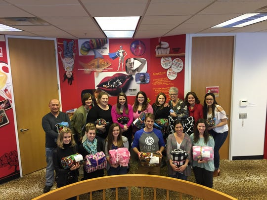The staff of Brogan & Partners and Fleece & Thank You director of operations Bryce Goulah (bottom row, third from right), with some of the blankets they made for patients of C.S. Mott Children's Hospital.
