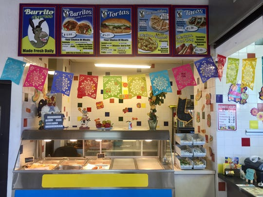 Colorful flags and menu images brighten the corner kitchen of Burrito Express in the Valero gas station food mart on East Fourth Street in Reno.