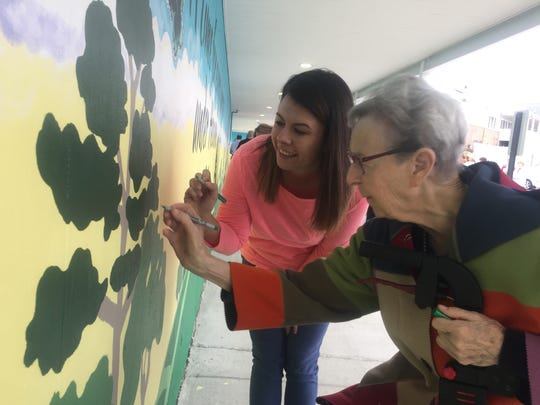 Christy Smith, Cedars activities coordinator, and Gladys Walker, Cedars resident, sign their name near their contribution to the new mural painted in Rolling Green Village, in honor of the community's 30th year.