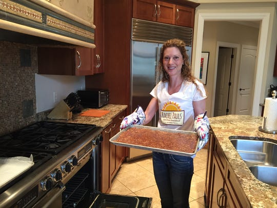 Dr. Rachel Pauls pulls a fresh batch of Happy Bars out of her oven.