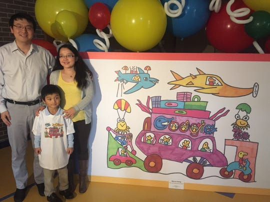 Marcus Zheng, 5, and his parents, Yi Zheng and Cathy Guo, with his winning Google doodle.