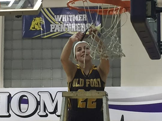 Old Fort's Peyton Miller cuts her piece of the net after a sectional championship.