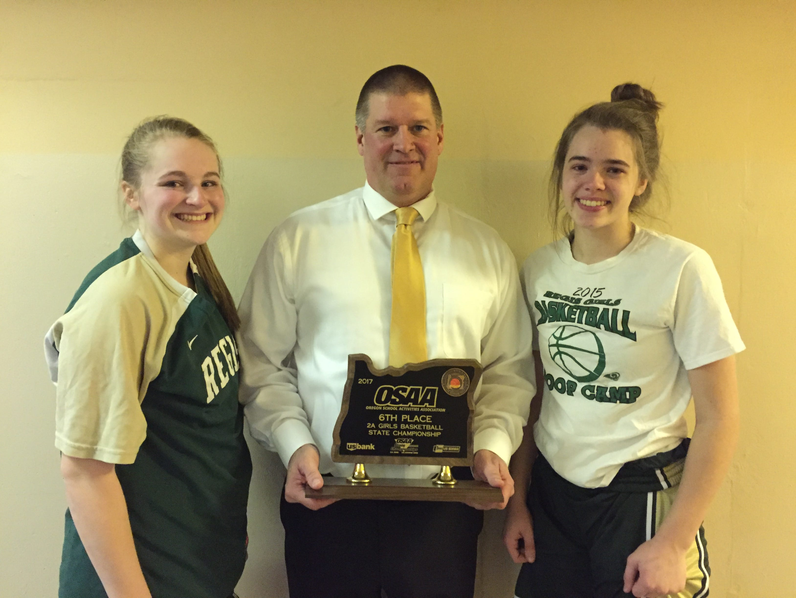 Regis girls basketball coach Stuart Alley, center, with seniors Hadyn Moll, left, and Victoria Clute with the 2A sixth-place trophy.