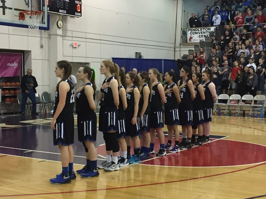 The Western Mennonite girls basketball team stands for the national anthem before Saturday's 2A state championship game at Pendleton Convention Center on March 4, 2017.