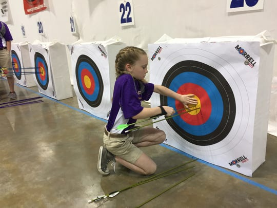 Benton's Hannah McKenzie pulls her arrows during a past Archery in Louisiana Schools state tournament at the Shreveport Convention Center.