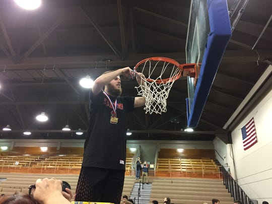 Senior forward Riley Nicot helpls cut down the net after Santiam won the OSAA Class 2A boys state championship at Pendleton Convention Center on March 4, 2017.