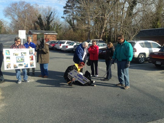 Protestors pause to pat Jake, a rescue dog owned by