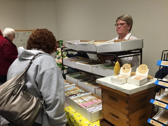 Ellen Harnish stands behind the counter for BeeOlogy, ready to answer customers' questions on hive-related products, in the vendor area of the  Raising Richland Community Garden Summit Thursday.
