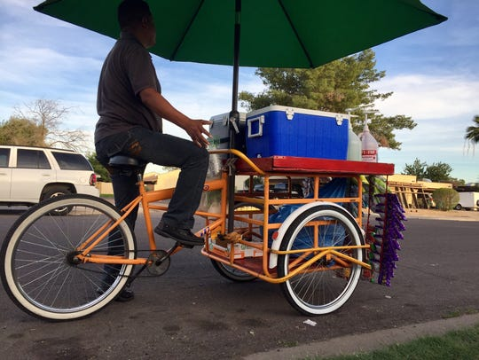 Carlos Zayas pedals his cart carrying corn, shaved