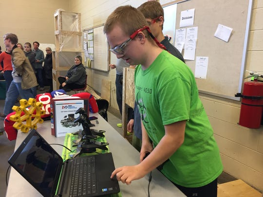 Alex Smith gives a robot instructions using his computer keyboard during a 4-H Robotics Club meeting on March 11, 2017.