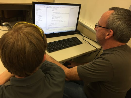4-H Robotics Club mentor John Baker, right,  works with Carson Seese on programming codes or drivers for one of the club's robots.