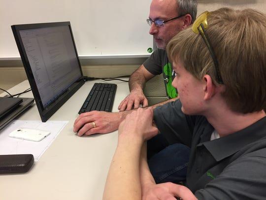 Programmer Carson Seese and mentor John Baker work