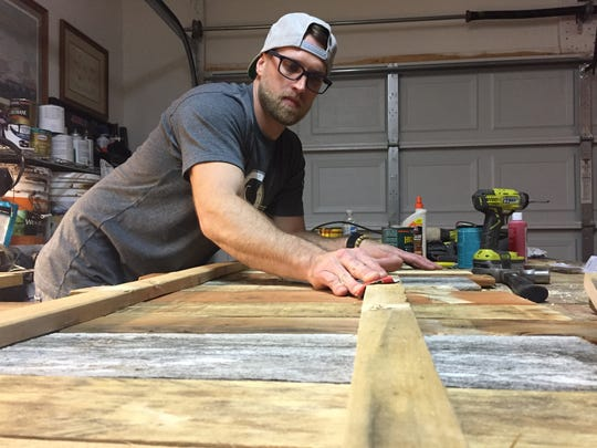 Justin Beshearse spends hours sanding and assembling salvaged wood to crate sign boards for his wife to decorate. They started JB Designs in Smyrna to sell their popular shabby chic decor.