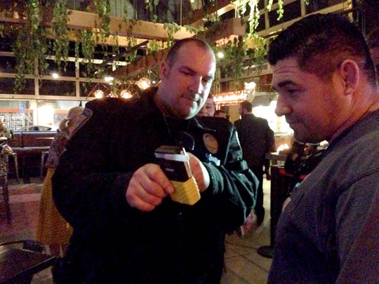 Officer Mike Wood shows Jason Bond, of Simi Valley, the results of his breathalyzer test on March 9 at Copper Blues in Oxnard.