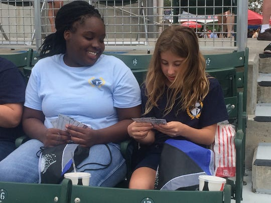 Eunica Castor and Emma Denich from De LaSalle Academy, check out their gift bats during the first Game Day Bunch, Inc., event, Feb. 23 at a Red Sox spring training game.