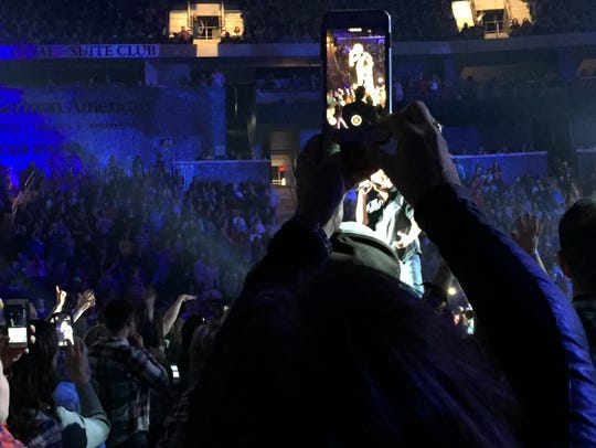 A fan takes a photo of Blake Shelton during Shelton's