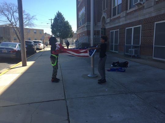 R.D. Wood Elementary School students fold the U.S. flag at the end of the Millville public school Friday afternoon.