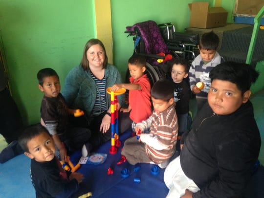 Whitney Schieltz, of the Sisters of Charity of Cincinnati plays with the siblings of children seeking care at a health clinic in the Anapra area of Juárez. She is doing her discernment in the El Paso area.