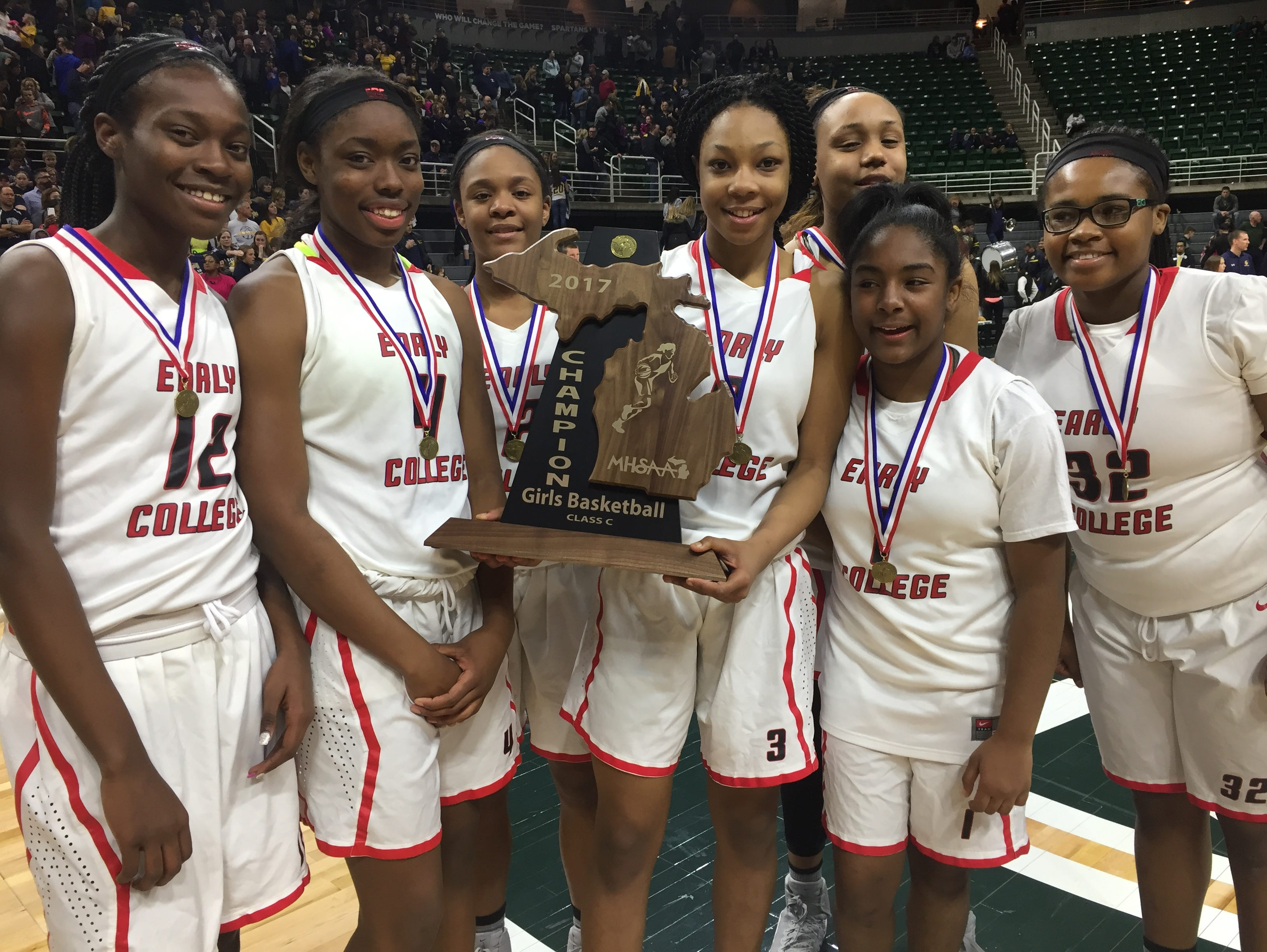 Detroit Edison freshman Gabrielle Elliott, joined by teammates, holds the Class C girls basketball state trophy after her team's 46-44 win over Pewamo-Westphalia at the Breslin Center on Saturday, March 18.