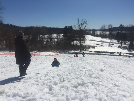 Kai Gibbons, 5, heads backward down the hill at Bowdoin County Park, as his mother, Jenn Gibbons, takes a photo. It was his first sled ride of 2017.