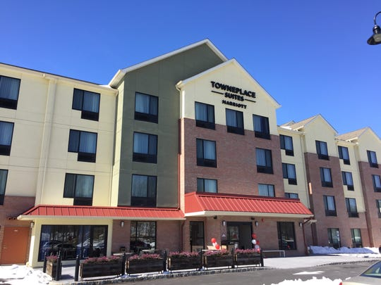Dover town officials and hotel staff cut the ceremonial ribbon Monday to officially open the new TownePlace Suites by Marriott Hotel in Dover's redevelopment zone.