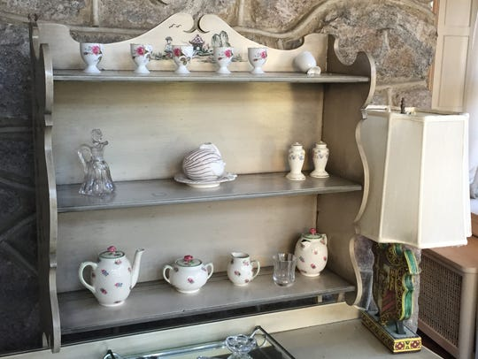 A tea-set is carefully arranged on a sideboard in a