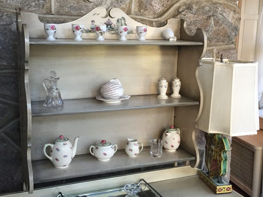 A tea-set is carefully arranged on a sideboard in a dining area at this Pelham Manor home.