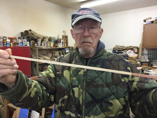 Jim Bradley shows one of the pieces of wood from which he makes crosses.