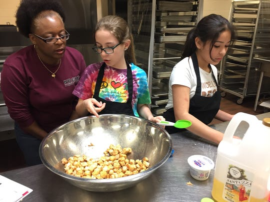 Junior Chef Academy helper Teresa Collier, left, talks with Karizma Long, center, and Irene Macias about what they're making.