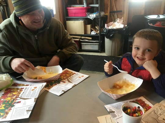 Aiden Jewett, 4, right, and father Nate Jewett of Williston enjoy sugar on snow at Sugartree Maple Farm in Williston on Sunday, March 26, 2017, during Maple Open House Weekend.