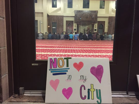 Members of the Islamic Center in Fort Collins are seen in March through the center's front doors.