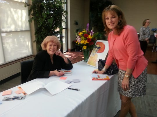 """Johnnie Lou Avery Boyd (left) signs a copy of her new book, """"MizHat: The Life Journey of Roy Helen Herndon Mingus Ackers,"""" for Kristi Thaxton."""