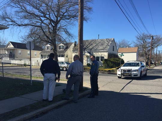 Investigators stood around a house on the 300 block of Fisher Avenue on Wednesday, after gunshots were fired into a car on Stratford Avenue in Neptune.