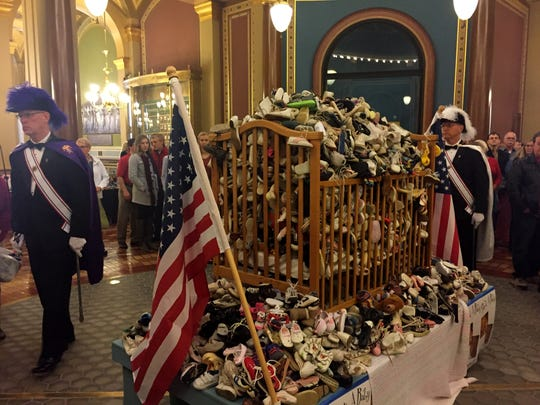 A Knghts of Columbus honor guard stands next to a display of thousands of baby shoes during an anti-abortion rally attended by about 500 people Thursday at the Iowa Capitol