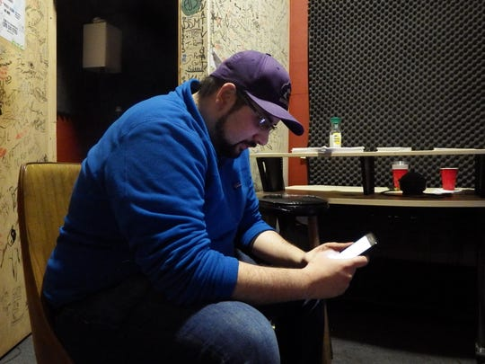 Sepehr Sadrzadeh writes lyrics on his cellphone in