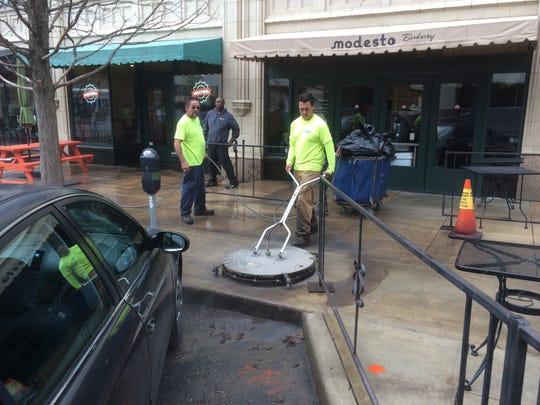 A crew from River Top Contracting cleans the sidewalks outside the Grove Arcade in mid-March.