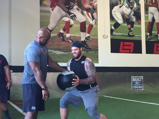 Lions tackle Taylor Decker, right, trains with former