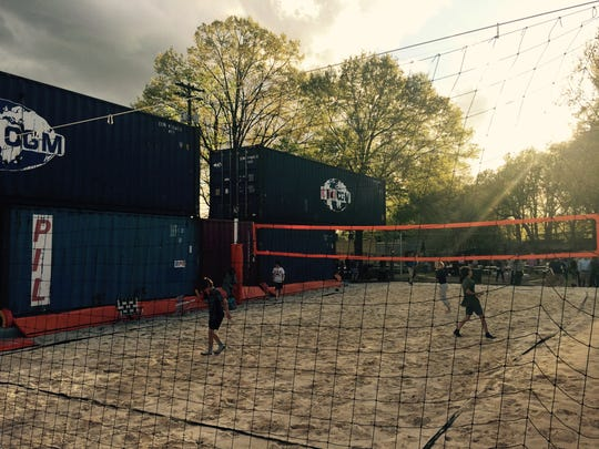 Sand volleyball court, shaded by railcars, at Railgarten (2166 Central Ave.).