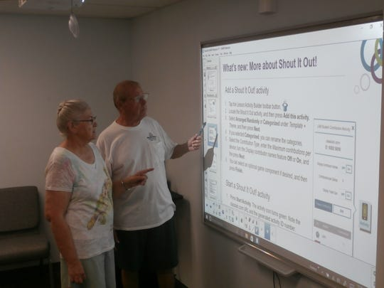 Diane and Dick Maher learn how to utilize the Smart Board system that's part of the Pine Island-based Beacon of HOPE's new classroom.