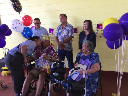88-year-old Jesus C. Babauta receives a kiss from a family member during a surprise ceremony Thursday awarding him with an honorary high school diploma which he was supposed to get 71 years ago were it not for World War II, among other things.