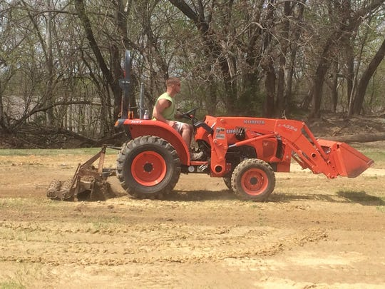 Brandon Bugg uses a tractor Sunday to work on the men's