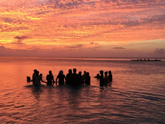 The Tiyan High School paddling team on April 12, 2017 at Matapang Beach hold hands for a bendision, or blessing, and hold a moment of silence for the JFK paddler who died on April 11, 2017.