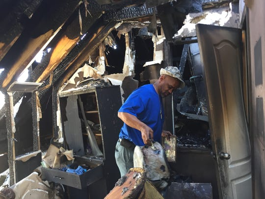 "Jerome Hood looks at items in his ""man cave"" destroyed"