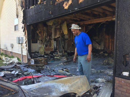 Jerome Hood looks at a Cadillac that was destroyed