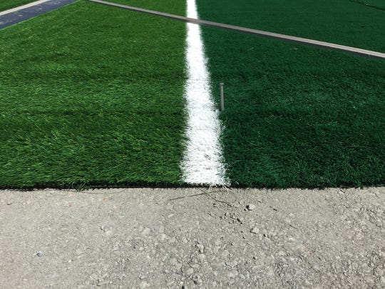 The first strips of artificial turf were put in place Thursday at CSU's new on-campus stadium, scheduled to open this fall.