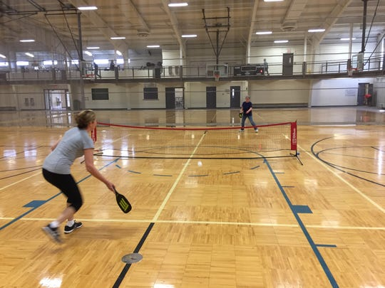 Melba Lozano, foreground, returns a serve from Linda Taylor as the two play pickleball, a hybrid game that blends tennis, table tennis and badminton, at the Fremont Recreation Center on Monday.