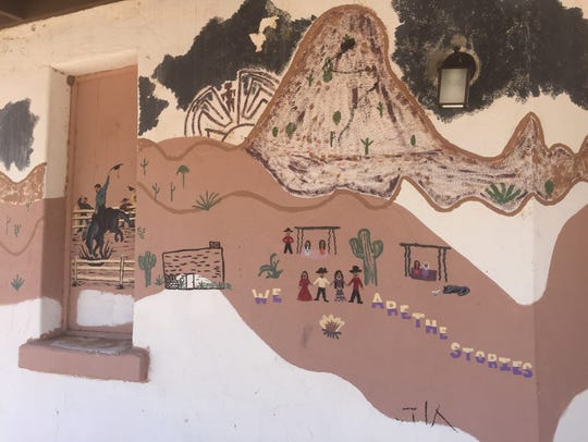 """A mural says, """"We are the stories,"""" on the outdoor"""