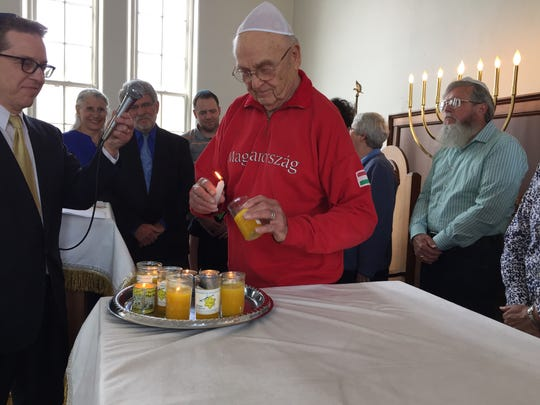 Franklin Scheib, a first-eneration member of an immigrant family from Hungary, lights a yellow candle in memory of those who died during the Holocaust. The ceremony was part of the community's 39th annual Holocaust Memorial Service.