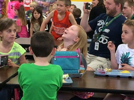 Lily Oldham (center) reacts Tuesday at Rosendale Primary School after finding out she won a national Scholastic Reading Club contest.
